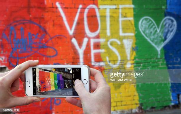 A passerby takes a photo of a Vote Yes mural supporting samesex marriage in Sydney on September 7 2017 Australia's High Court on September 7 threw...