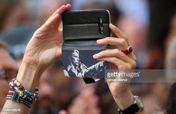 A passerby takes a photo of the commemmorative plaque for David Bowie at Hauptstrasse 155 in Berlin Germany 22 August 2016 The rockstar lived there...