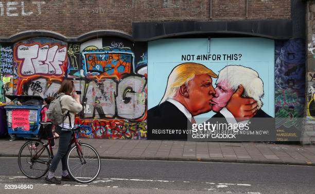 Passer-by takes a photograph of a mural showing likely US Republican presidential nominee Donald Trump kissing the Former Mayor of London and...