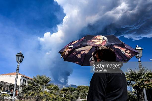 Passer-by takes shelter from the ash and lapilli caused by Etna's eruption in a square in Trecastagni on February 19, 2021 in Catania, Italy. Strong...