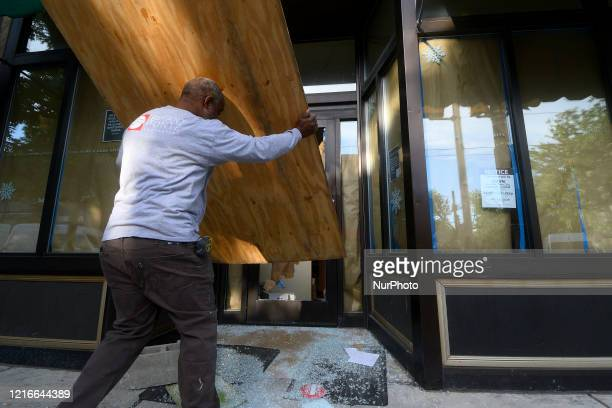 A passerby voluntarily boards up the stateowned wine and liquor store after it is vandalized overnight in the Mt Airy neighborhood in Philadelphia PA...