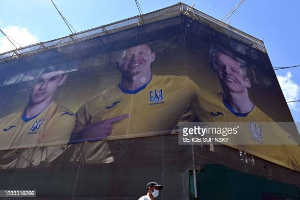 Passer-by walk past billboard showing Ukrainian National football team in Kiev on June 7, 2021. - Ukraine provoked Moscow's ire on June 6 as its...