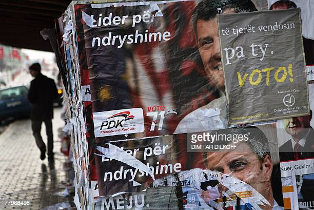 A passerby walks by ripped election posters featuring the leader of the Democratic Party of Kosovo Hashim Thaci in Pristina 18 November 2007 Thaci a...