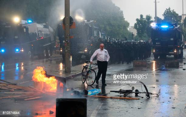 A passerby walks his bike past burning waste bins and riot police using water cannon against protesters on July 7 2017 in Hamburg northern Germany...