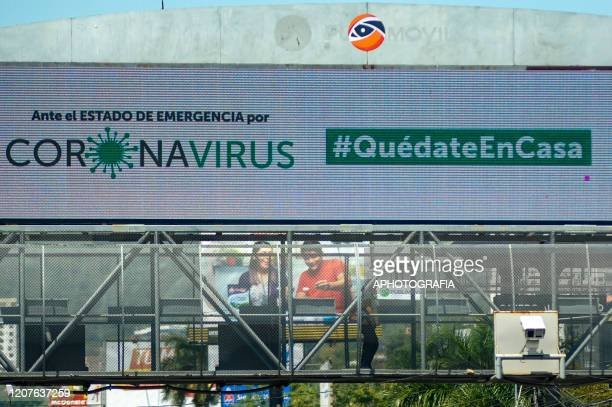 A passerby walks on a pedestrian bridge as an ad displays measures against coronavirus on March 18 2020 in San Salvador El Salvador Despite no cases...
