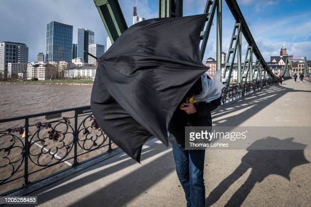 A passerby walks over the bridge 'Eiserner Steg' during high winds from storm Sabine on February 10 2020 in Frankfurt Germany The storm called Ciara...