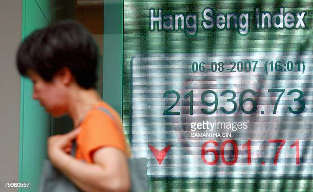 A passerby walks past the Hang Seng Index shown on a giant digital screen at a local bank's window in Hong Kong 06 August 2007 The Hang Seng Index...
