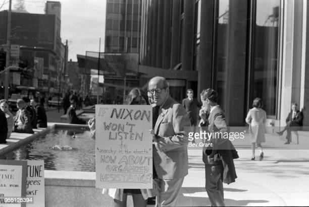 A passerby watches as a young woman holds a sign that reads 'If Nixon Won't Listen to Anarchy in the Streets How About Organized Resistance'outside...