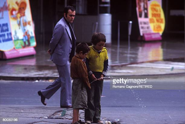 A passerby watches two homeless boys urinating in the street in Bogota Colombia circa 1990