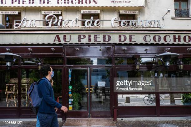 Passerby wearing a face mask, walks in front of a closed Au Pied de Cochon as the lockout continues due to the epidemic of coronavirus on May 23,...