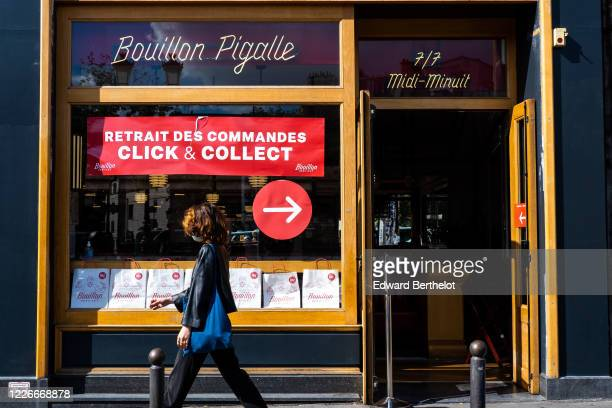 Passerby wearing a face mask, walks in front of the Bouillon Pigalle which is only opened for take-away food as the lockout continues due to the...