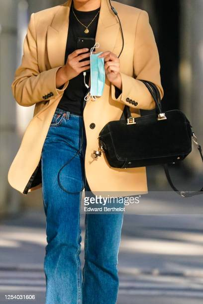 A passerby wears a beige oversized blazer jacket a golden necklace a black tshirt a bag blue jeans on June 28 2020 in Paris France