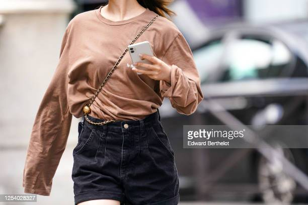 A passerby wears a beige / pale brown oversized top with long sleeves a crossbody bag black denim shorts on June 28 2020 in Paris France