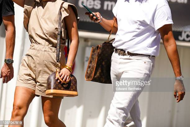 Passerby wears a beige ruffled short jumpsuit, a brown leather Vuitton monogram bag, a golden bracelet ; a passerby wears a white t-shirt, a snake...