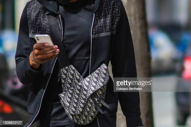 Passerby wears a black and gray Fendi monogram print jacket, a Dior Saddle bag, a black t-shirt, on March 28, 2021 in Paris, France.