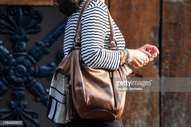 A passerby wears a black and white striped pullover a brown leather bag on June 28 2020 in Paris France