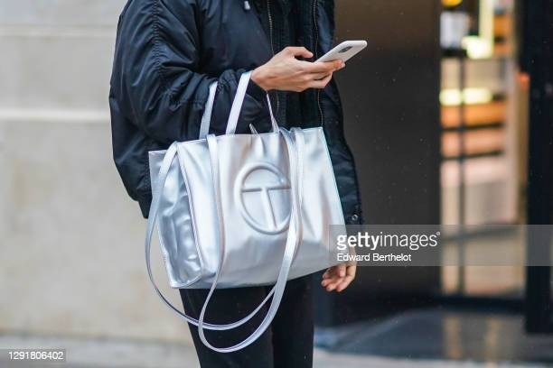 Passerby wears a black bomber jacket and a silver Telfar logo large bag, on December 12, 2020 in Paris, France.
