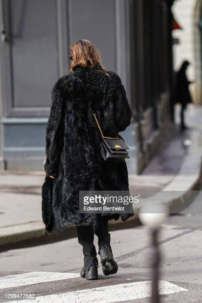 Passerby wears a black long fur fluffy coat, a black leather Balenciaga bag, black shoes, on January 28, 2021 in Paris, France.