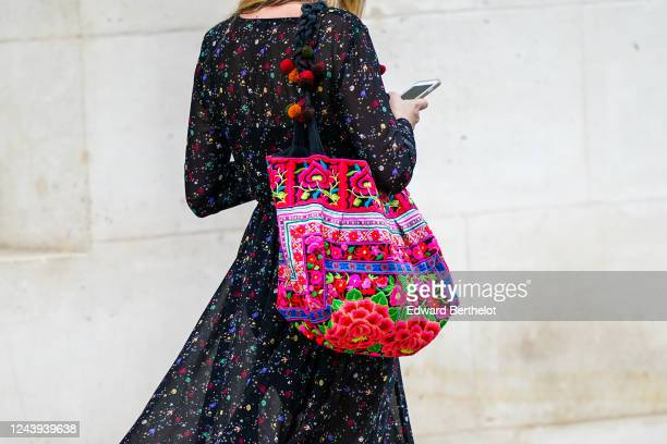 A passerby wears a black mesh flowing dress with colorful floral print a neon multicolor floral print bag on June 03 2020 in Paris France
