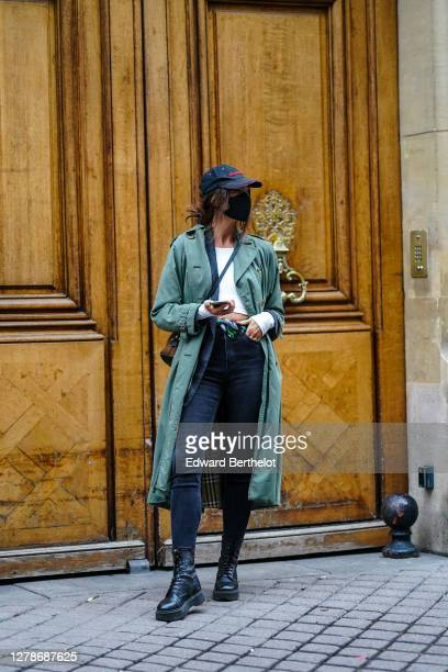 Passerby wears a black protective face mask, a green trench coat, a white cropped top, black jeans, leather boots, a cap, during Paris Fashion Week -...