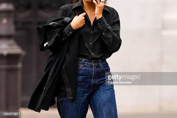 Passerby wears a black shirt, a black jacket, blue denim jeans, on July 04, 2020 in Paris, France.