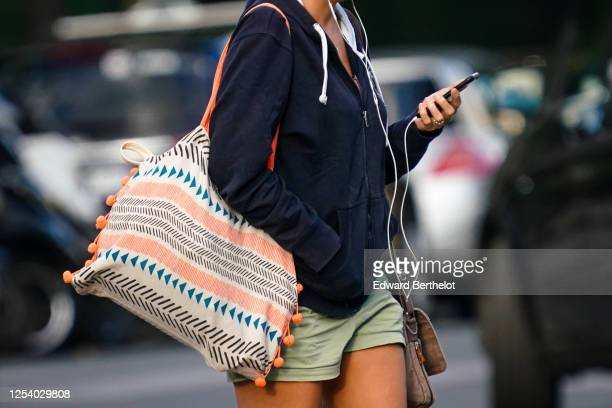 A passerby wears a black sweater a short green dress a large tote bag with pompoms and printed patterns on June 28 2020 in Paris France