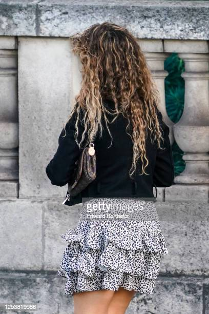 A passerby wears a black vest a brown leather Vuitton monogram small bag a black and white ruffled leopard print short skirt on June 28 2020 in Paris...