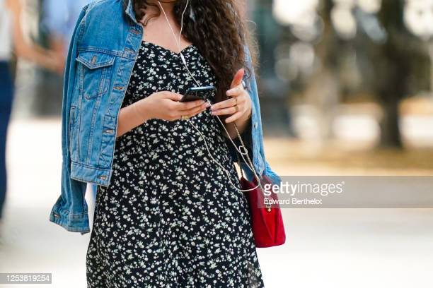 A passerby wears a blue denim jacket a black and white floral print dress a red bag on June 28 2020 in Paris France
