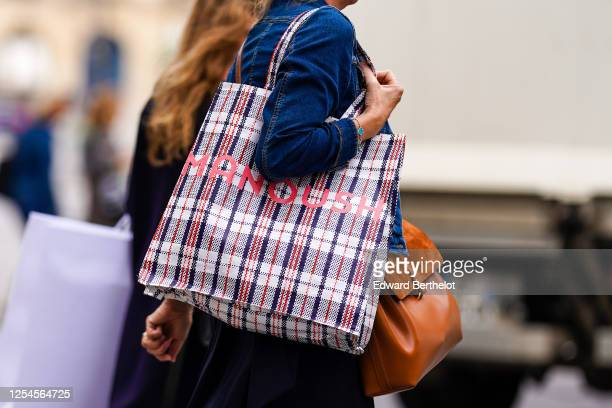 Passerby wears a blue denim jacket, a brown leather bag, a blue and red checkered large shopping bag from Manoush, on July 04, 2020 in Paris, France.