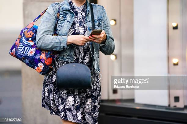 Passerby wears a blue denim jacket, a purple floral print Monoprix shopping bag, a black and white short dress with printed feathers, a black leather...
