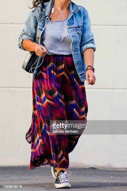A passerby wears a blue denim jacket a purple pleated skirt with printed geometric patterns sneakers on June 28 2020 in Paris France