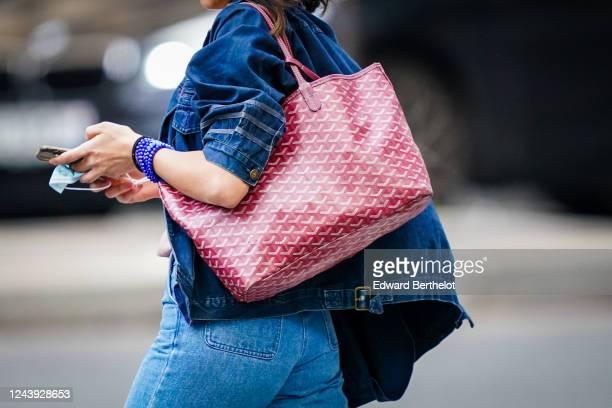A passerby wears a blue denim jacket blue jeans a burgundy Goyard leather large monogram bag on June 03 2020 in Paris France