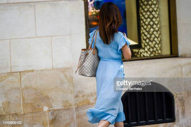 A passerby wears a blue pleated ruffled flowing dress a Louis Vuitton gray checkered print large bag on June 03 2020 in Paris France