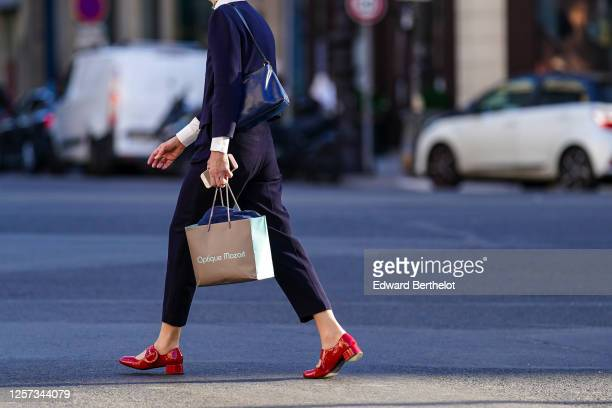 Passerby wears a blue pullover, cropped pants, red shiny shoes, a shopping bag, on July 08, 2020 in Paris, France.