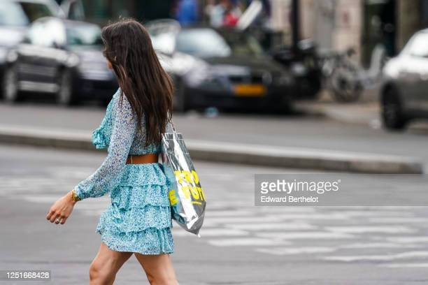 A passerby wears a blue ruffled dress a brown leather belt a silver bag on June 20 2020 in Paris France