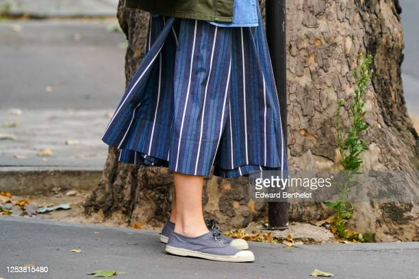 A passerby wears a blue striped skirt gray flat sneakers on June 28 2020 in Paris France