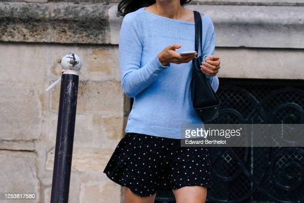 A passerby wears a blue wool pullover a black skirt a black leather bag on June 28 2020 in Paris France