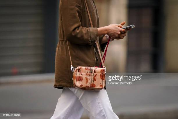 A passerby wears a brown jacket a leather pink and brown/beige crocodile pattern bag white pants on June 28 2020 in Paris France