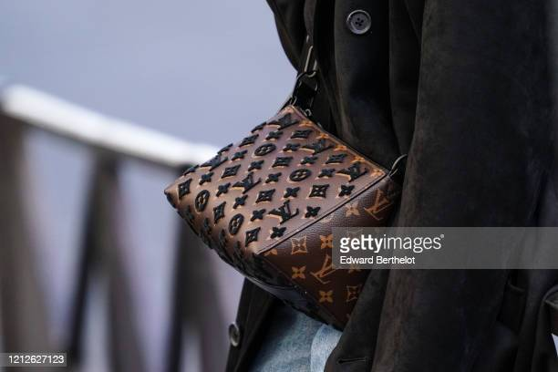 Passerby wears a brown Vuitton monogram bag, in the streets of Paris, on March 15, 2020 in Paris, France.