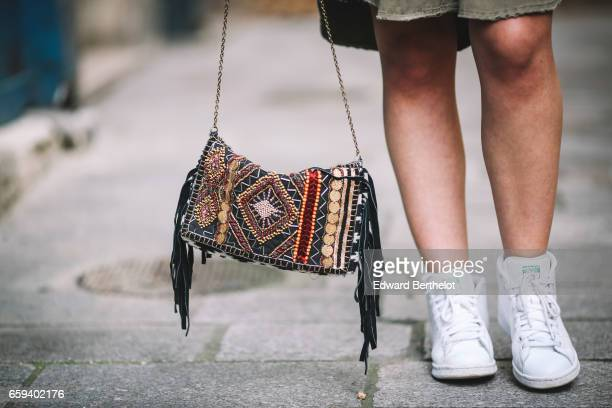 A passerby wears a colored bag with fringes and white Adidas Stan Smith sneakers shoes on March 26 2017 in Paris France