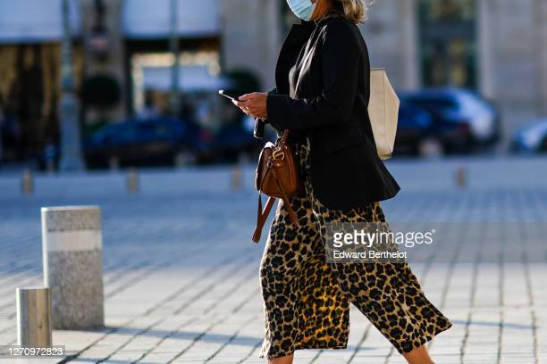 Passerby wears a face mask, a black blazer jacket, a brown leather bag, flared leopard print pants, on September 02, 2020 in Paris, France.