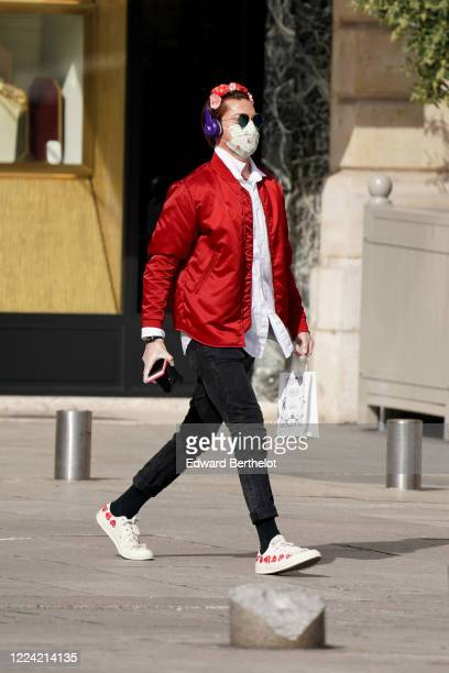 Passerby wears a face mask, floral headband, purple Bose headphones, a red bomber jacket, a white shirt, black pants, CDG Comme des Garçons sneakers...