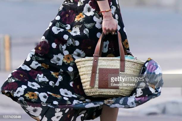 Passerby wears a floral print flowing dress, a Loewe straw bag with brown leather handle, on May 27, 2020 in Paris, France.