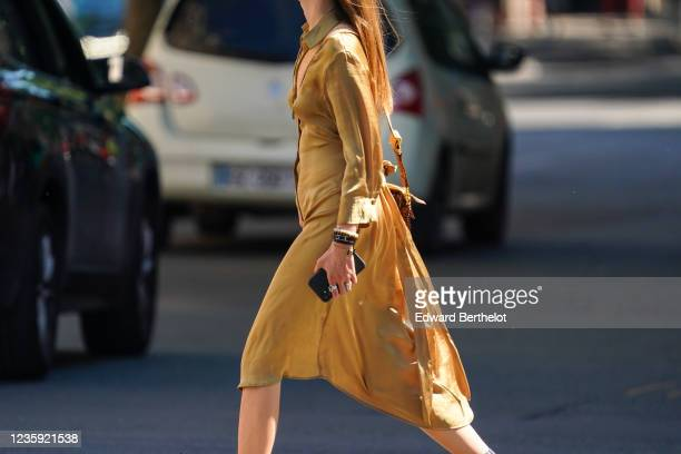 Passerby wears a golden colored lustrous silky dress, bracelets, on May 30, 2020 in Paris, France.