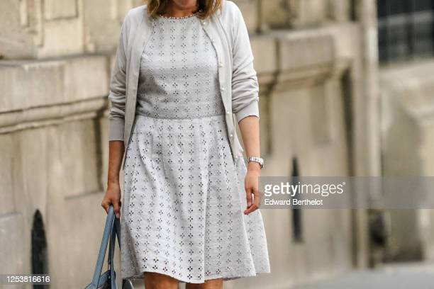 A passerby wears a gray wool vest a dress with embroidery a watch on June 28 2020 in Paris France