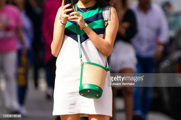 A passerby wears a green blue and white striped dress a green a brown bag a watch on June 28 2020 in Paris France