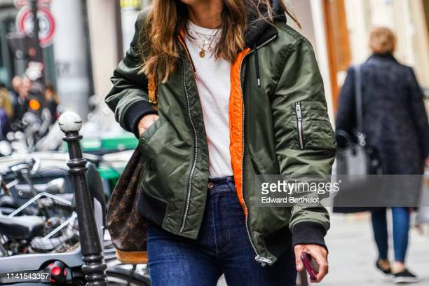 Passerby wears a green bomber jacket with orange inner lining, a Vuitton monogram bag, blue denim jeans, on April 01, 2019 in Paris, France.