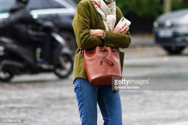 A passerby wears a green jacket a brown leather bag blue jeans a scarf outside Miu Miu during Paris Fashion Week Womenswear Spring Summer 2021 on...