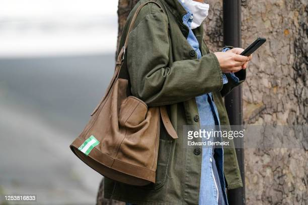 A passerby wears a green khaki jacket a brown leather bag on June 28 2020 in Paris France