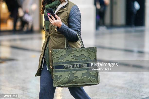 Passerby wears a green scarf, a green khaki Christian Dior military camouflage shopping large bag, a jacket with khaki parts and black leather...